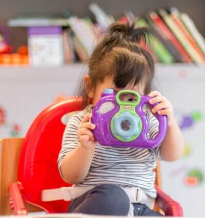 educational toys for 6 year olds- young girl with a camera in her hands