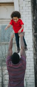 father tossing boy in the air