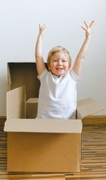 best monthly subscription boxes for kids- kid standing in a box with hands raised